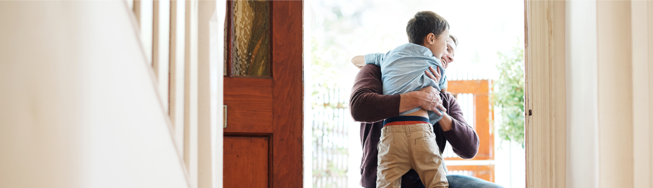 Son hugging father in doorway
