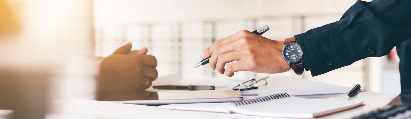 Man's hand holding pen above desk strewn with financial statements