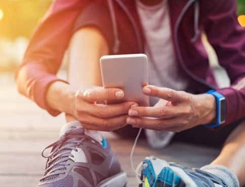 Picture of a mobile phone being held by man sitting on ground