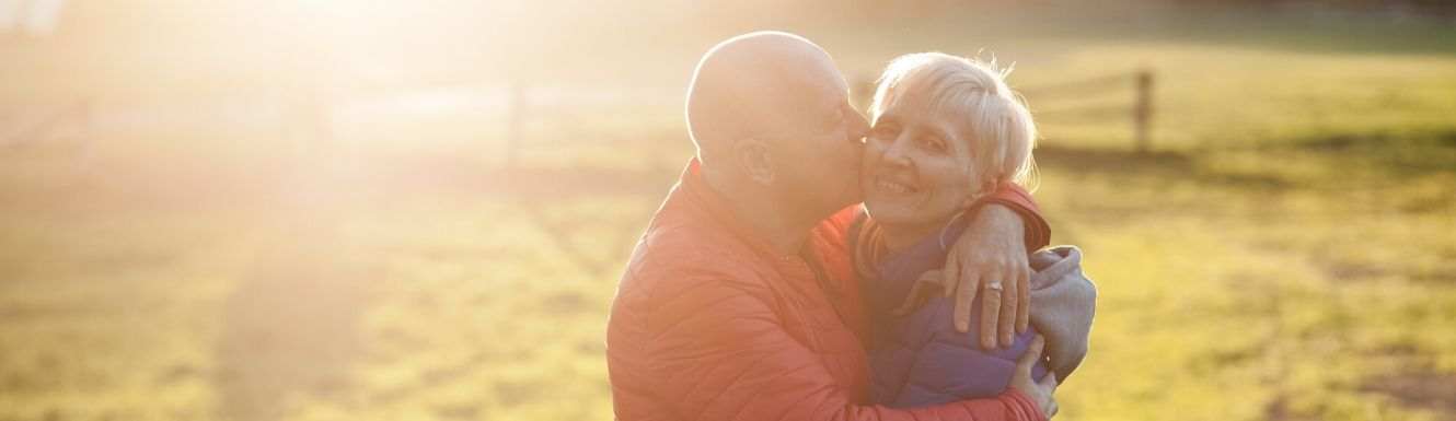 Retired couple standing in field while man kisses woman on cheek