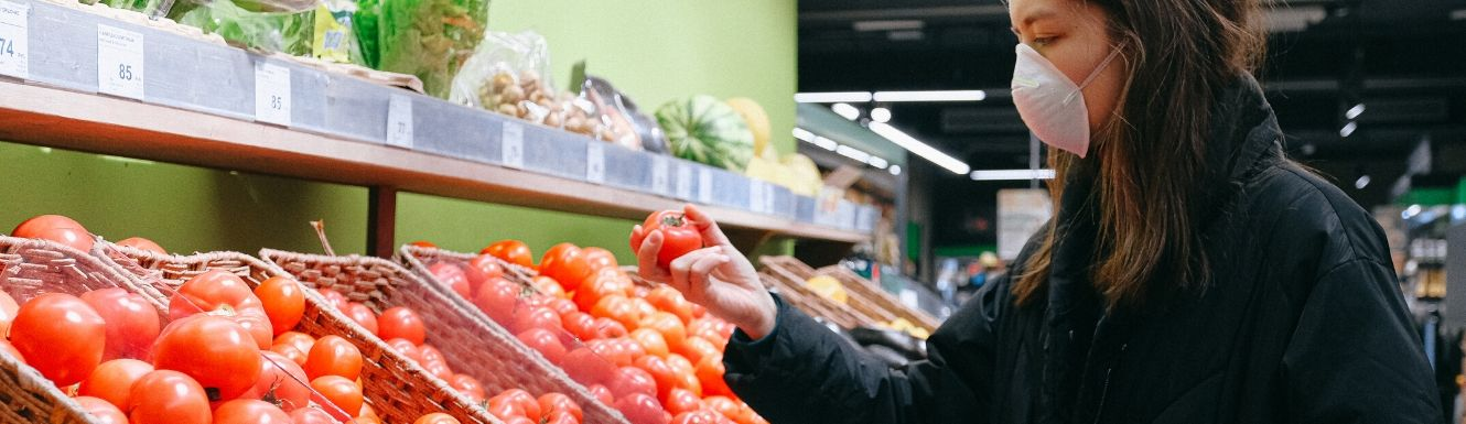 Woman in a face mask selecting tomato in grocery produce section