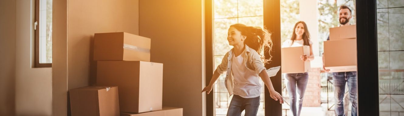 Man and woman moving into home while daughter runs in ahead of them