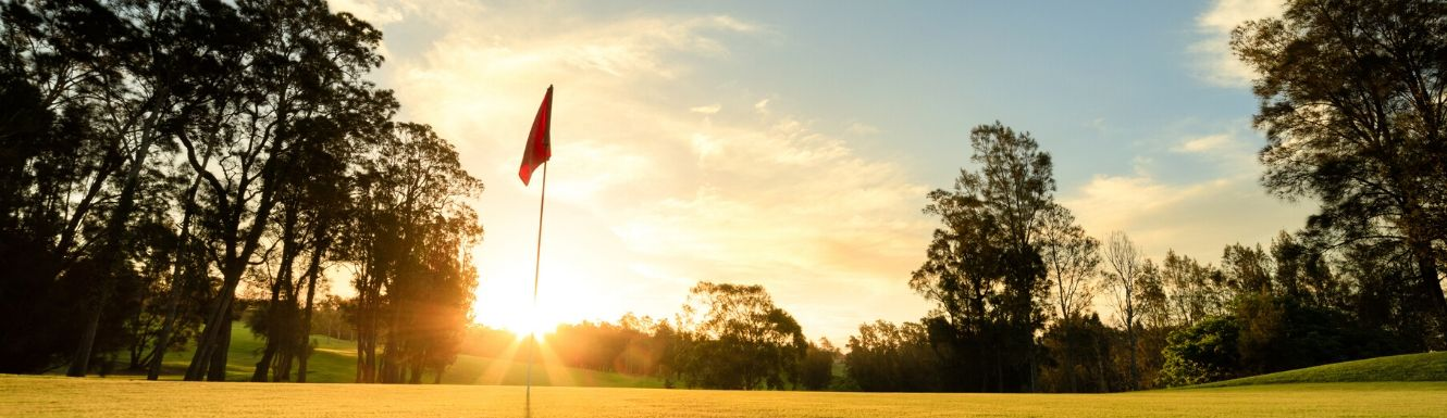 Flag in the hole on golf course with sun setting